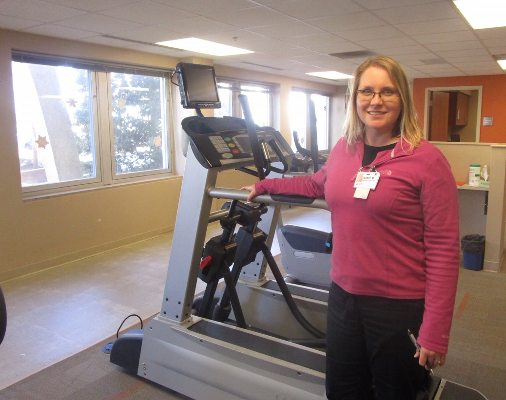 Mandy Marshall stands in front of a treadmill