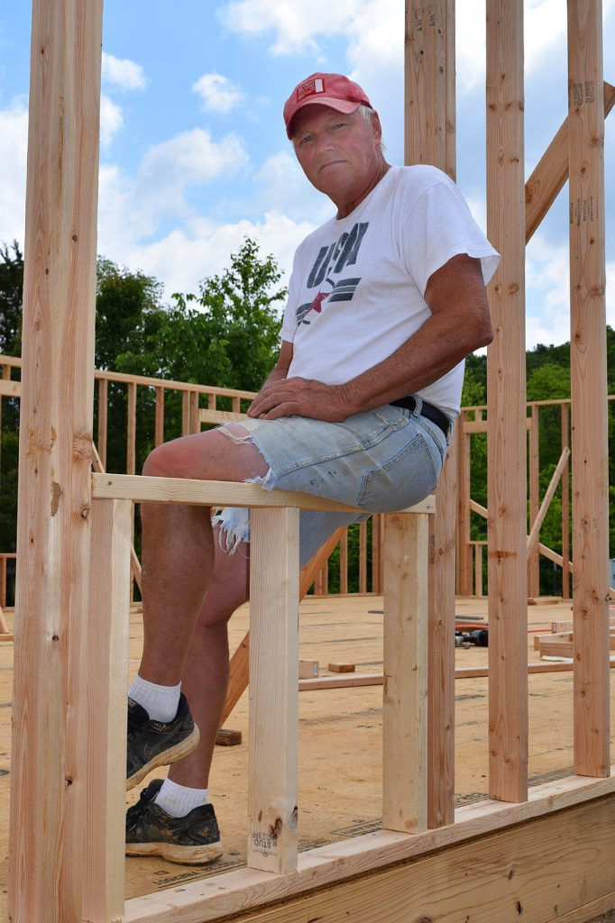 Micahel Smith sits on frame of house