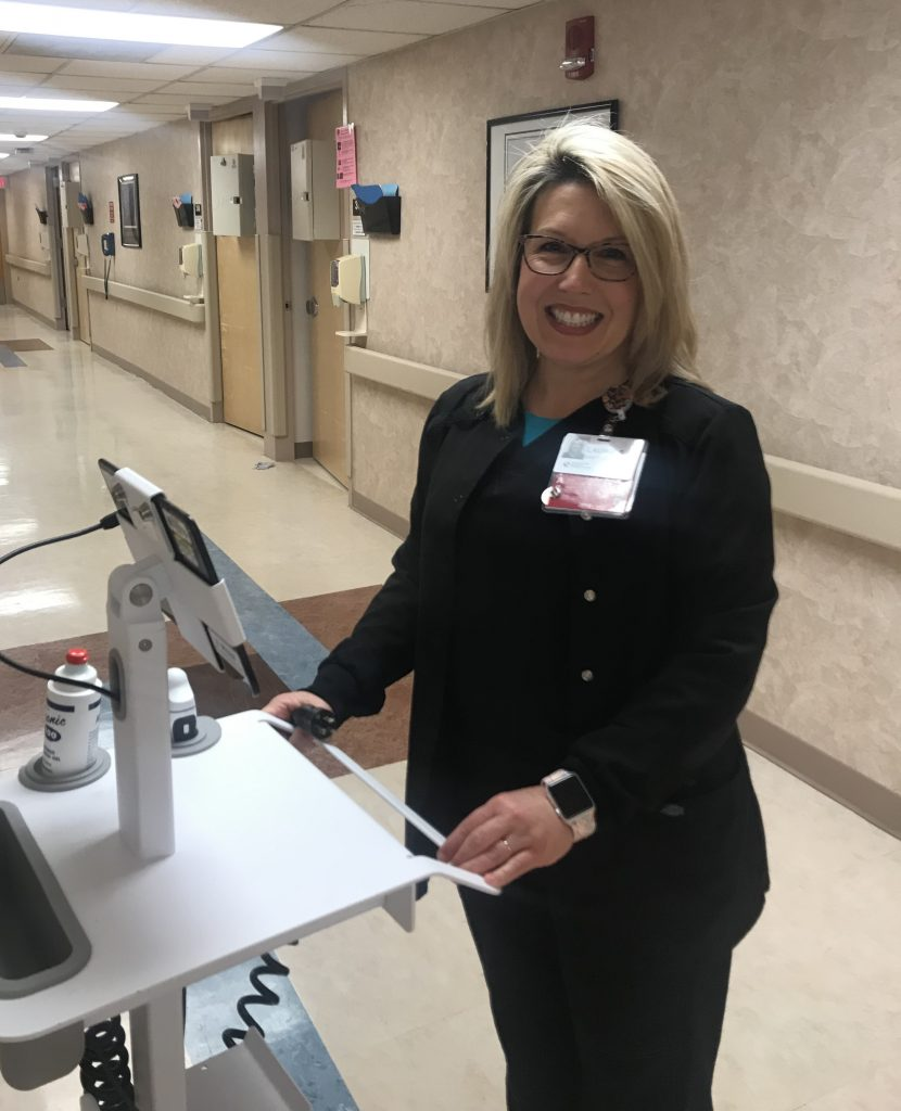 Laurie Somers stands with medical equipment in the nephorology unit