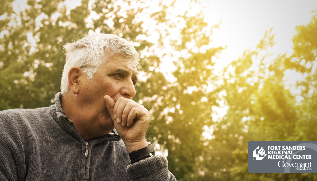 Man coughing with trees behind him due to COPD
