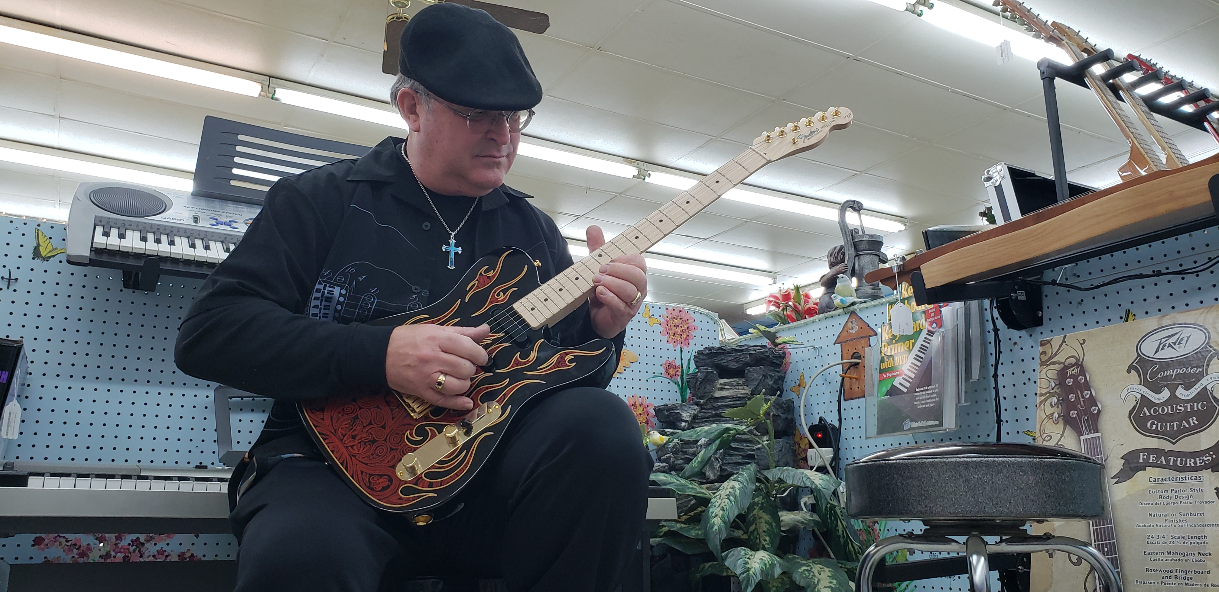 Smith strumming on his guitar at his pawn shop